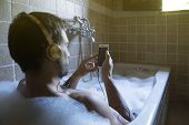 Naked Guy In Bathroom With Smartphone And Headphones poster