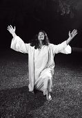 foto of glorify  - A biblical man bowed on one knee in a garden arms raised to heaven glorifying God - JPG