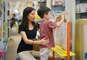 Young Asian Mother And Her Kid Shopping Toy In Shopping Mall poster