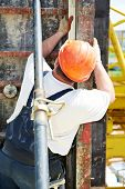builder worker at construction site checking formwork with level measuring equipment poster