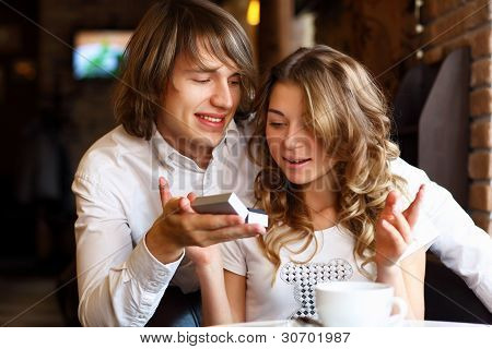 Young couple with engagement ring in a restaurant