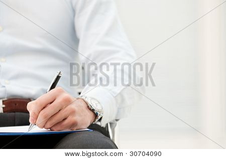 Closeup of business man writing form on clipboard at office