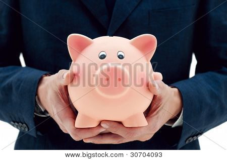 Businessman holding a piggy bank in his hands symbol of savings and good investments