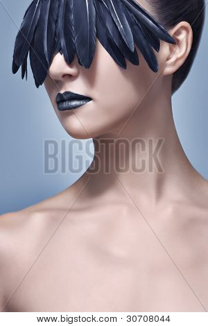 Glamour and beauty shot of a beautiful model with creative make-up of black bird feathers concealing her eyes like a mask. High-end retouching.