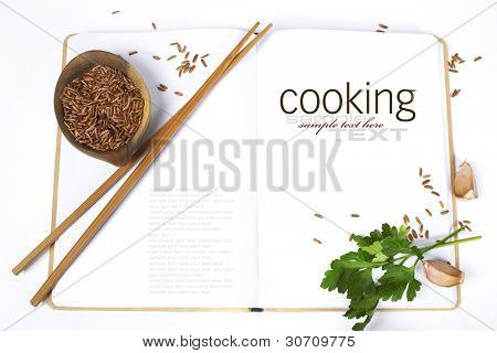 uncooked rice,  chopsticks, garlic, parsley and opened notebook (with easy removable sample text)