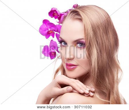 beautiful young woman with long curly hair and an orchid, isolated against white studio background, copy space for your text to the left