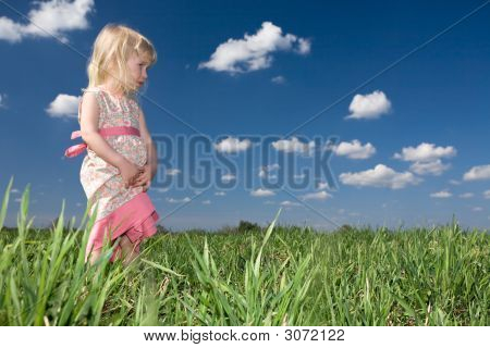 Toddler Girl On Green Meadow