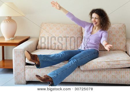 Beautiful laughing woman jumped on couch in simple comfortable room