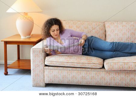 Beautiful young woman lies on couch in simple room and look at journal