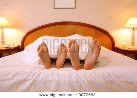 Woman and man rest on soft big bed with white sheets; focus on feet