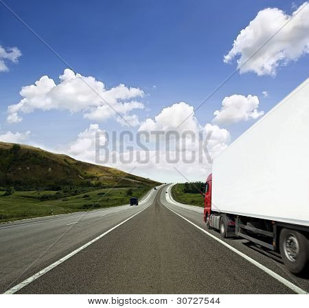 Red truck on asphalt road over blue cloudy sky background