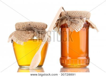 Sweet honey in jars with spoon isolated on white