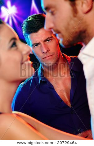 Angry jealous man looking at young dancing couple in nightclub.?