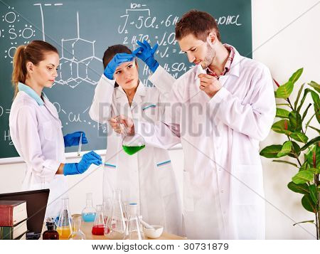 Group chemistry student with flask in classroom.