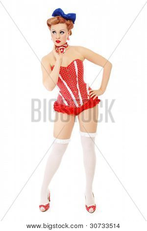 Beautiful young sexy pin-up girl in polka dot corset looking aside with thoughtful expression, on white background
