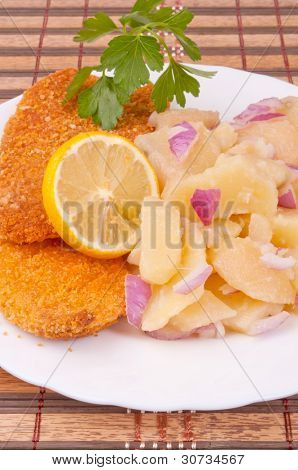 Breaded hake fillets and boiled potato salad with red onion
