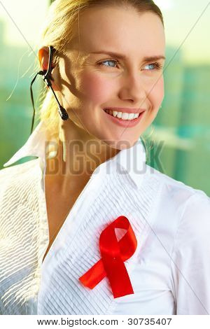 Portrait of smiling woman with headset and red ribbon on blouse