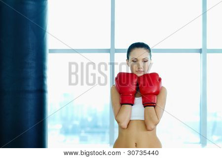 Portrait of sad young woman in red boxing gloves in gym