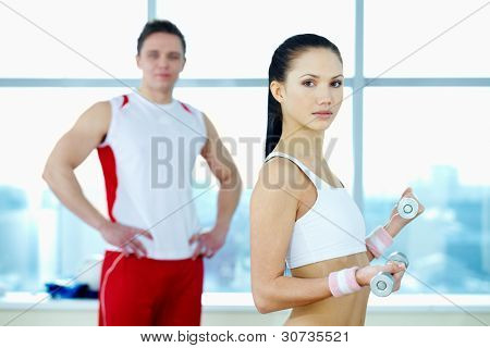 Image of fit woman holding with barbells with young guy on background