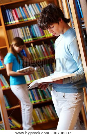 Tilt up shot of two teens reading books at library