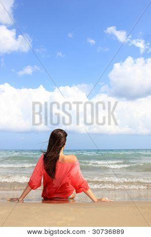 Woman in bikini wearing a red shirt relax on the beach