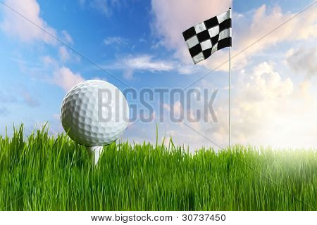 Golf ball with tee in the grass with flag against blue sky