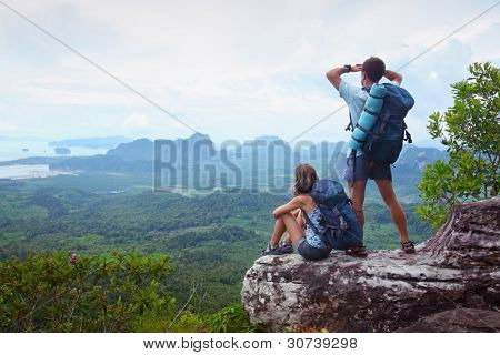 Backpackers on top of a mountain enjoying valley view
