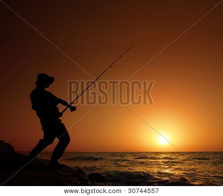 A young fisherman fishing with sunset in the background