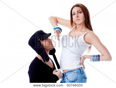 Young man kneeling in front of beautiful brunette, woman showing him rejection hand sign