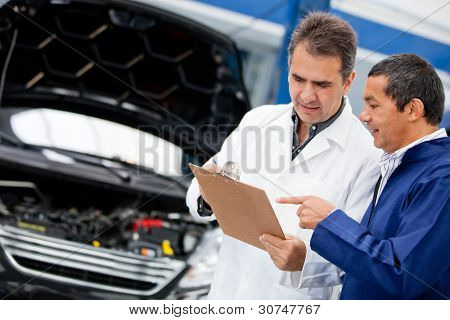 Male mechanics talking about fixing a car