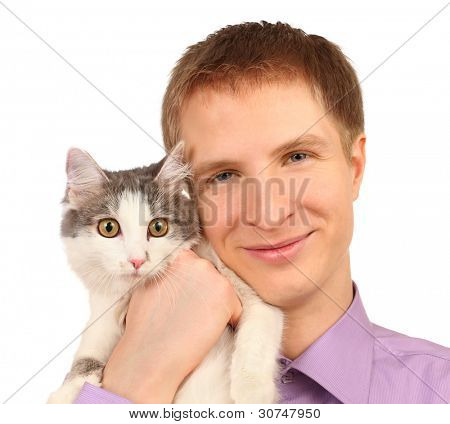Smiling young man holds surprised cat isolated on white background
