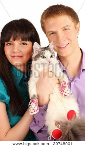 Smiling young man and woman hold cat wearing in red boots isolated on white background