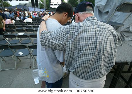 NEW YORK - JUNE 25:  A religious counselor (R) prays with a young man as they attend the Greater New York Billy Graham Crusade at Flushing Meadows Corona Park on June 25, 2005 in Flushing, New York.