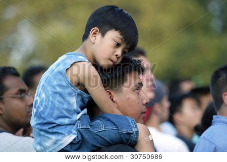 NEW YORK - JUNE 25:  A child sits on his father's shoulders as they attend the Greater New York Billy Graham Crusade at Flushing Meadows Corona Park on June 25, 2005 in Flushing, New York.