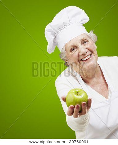 cozinheiro sênior mulher oferecendo uma maçã verde contra um fundo verde