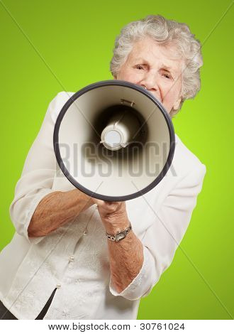 portrait of senior woman screaming with megaphone over green background