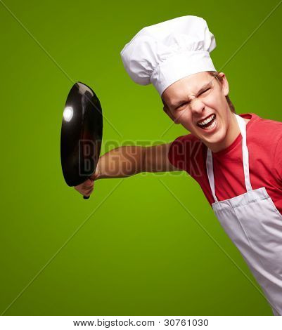 portrait of angry young cook man hitting with pan over green background