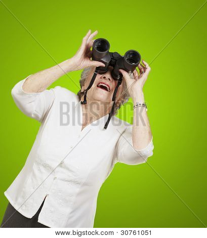 portrait of senior woman looking through a binoculars against a green background