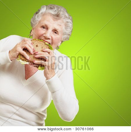 portrait of senior woman eating vegetable sandwich over green background