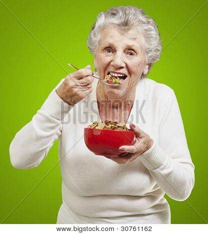 senior woman eating cereals out of a red bowl against a green background