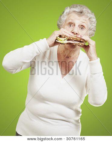 Senior Woman Essen einer gesunden Sandwich vor einem grünen Hintergrund
