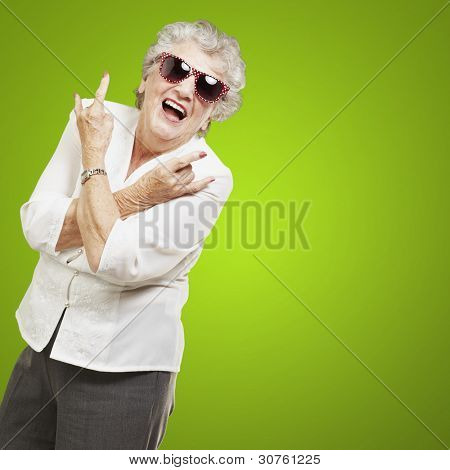 portrait of senior woman doing rock symbol over green background