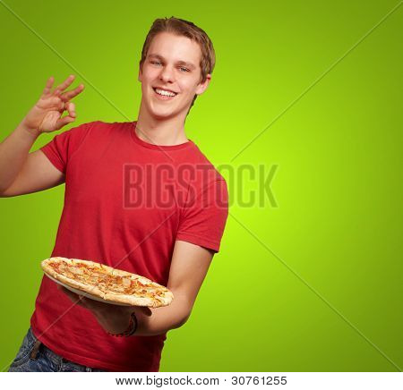 portrait of young man holding pizza and doing good gesture over green background