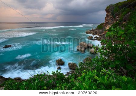 Rocky coast of Indian ocean at sunset light. Bali island. Indonesia