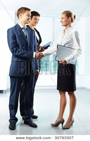 Vertical full-length shot of business people shaking hands with a smile