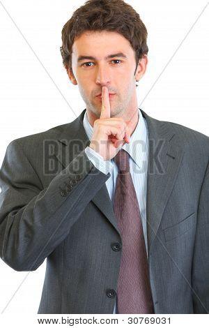 Retrato de homem de negócios moderno, mostrando o gesto do Shh