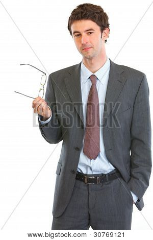 Thoughtful Businessman Holding Eyeglasses