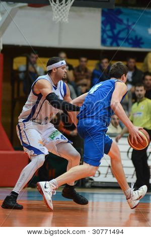 KAPOSVAR, HUNGARY â?? FEBRUARY 18: Michael Fey (in white) in action at a Hungarian Championship basketball game with Kaposvar (white) vs. Zalaegerszeg (blue) on February 18, 2012 in Kaposvar, Hungary.