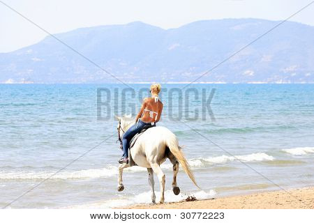 Beautiful blonde woman in bikini in the sea in Greece riding a white horse