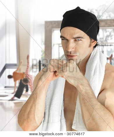 Portrait of a serious muscular male fitness model inside gym with fists raised to box wearing a hat and towel with blurred background of active sports gym